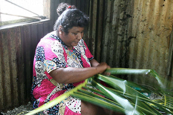 Marshallese woman making basket with coconuts leaves