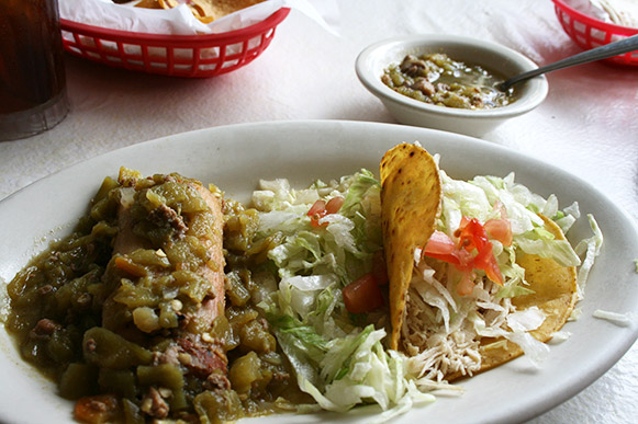 Mary and Tito's Tamale with green chili sauce and chicken taco